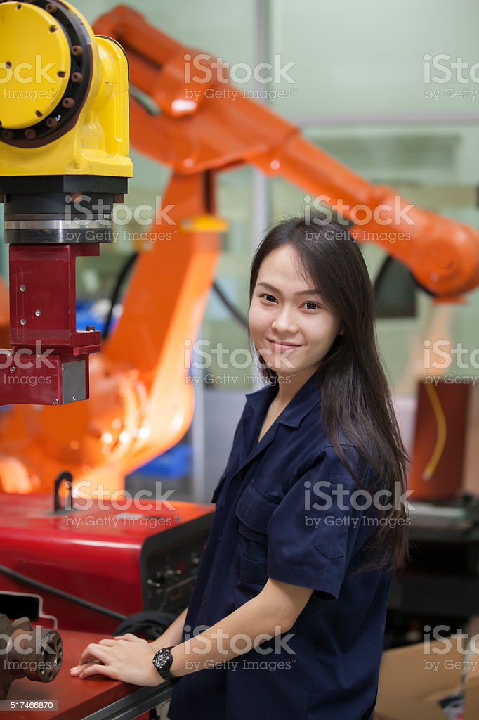 Manufacturing worker operating a robot machine stock photo