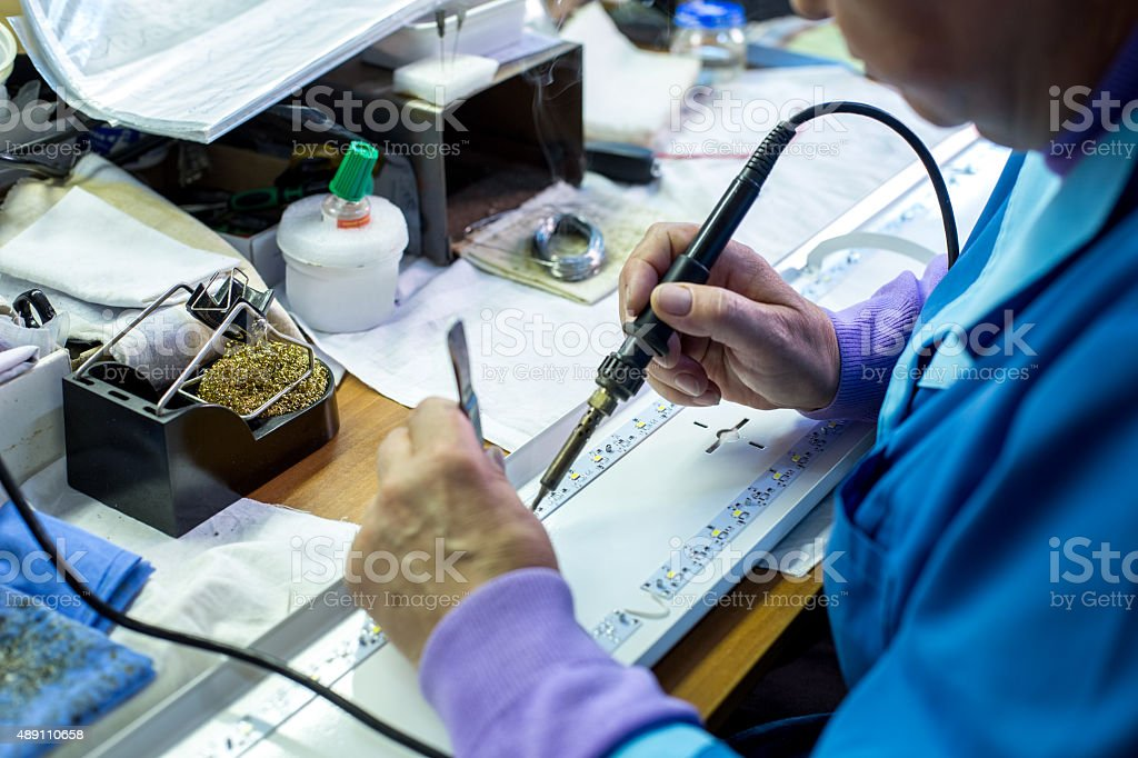 Manufacturing. Worker soldering circuit board stock photo