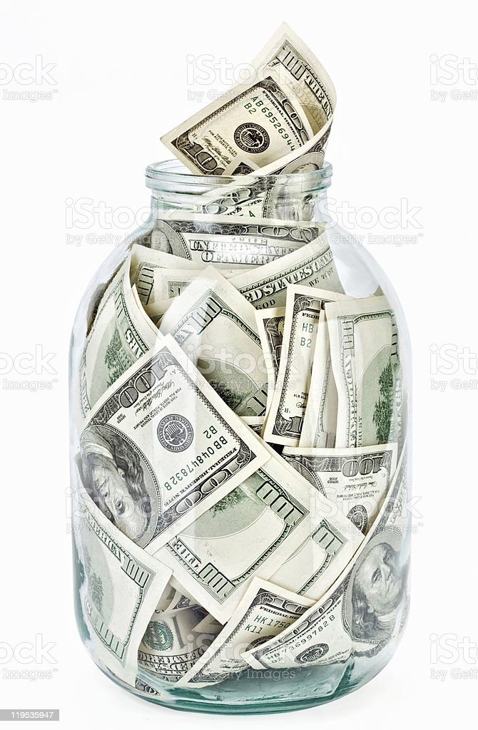 Many 100 US dollars bank notes in a glass jar stock photo