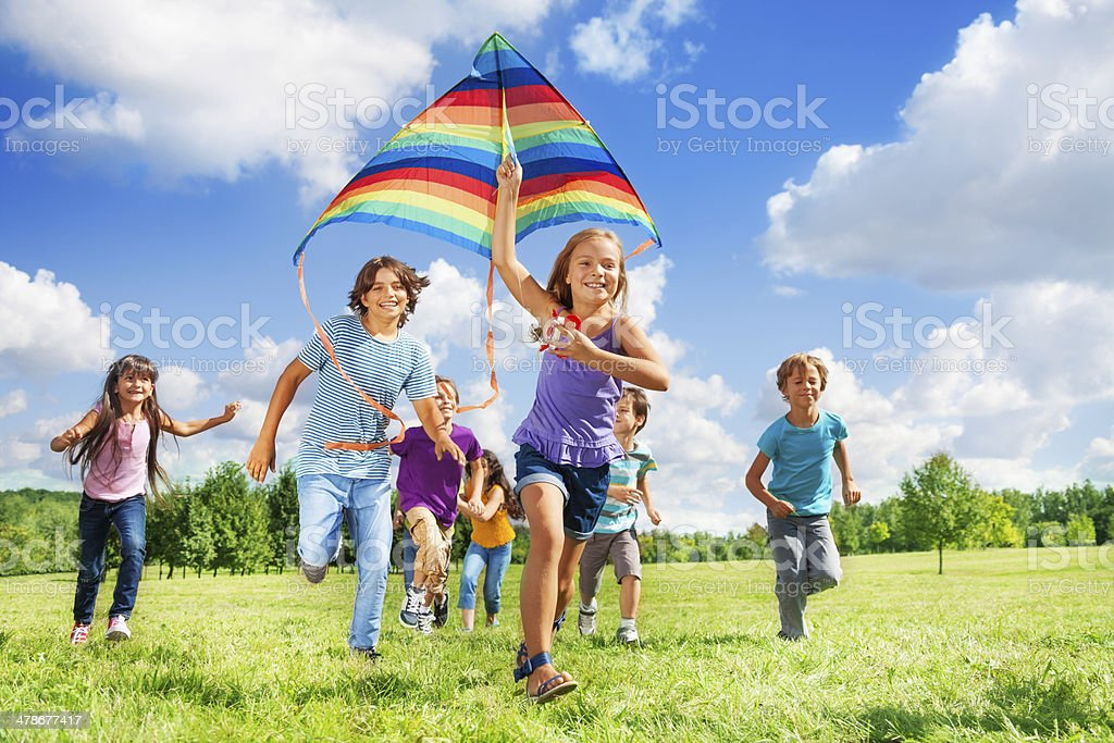 Many active kids with kite stock photo