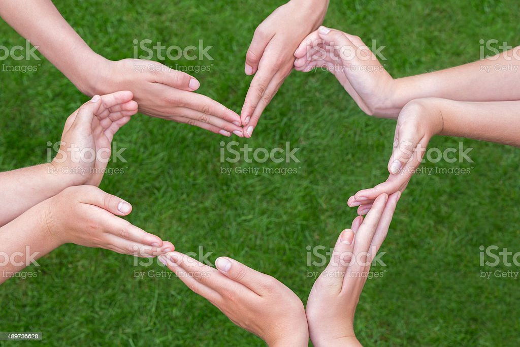 Many arms of children construct heart above grass stock photo