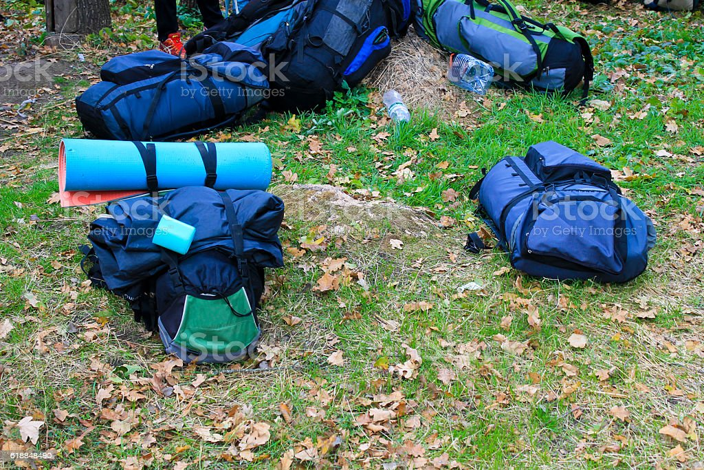 Many backpacks of hikers on a meadow stock photo