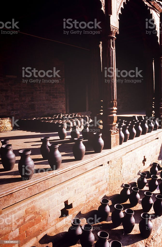 Many black pottery vases lined up on wooden platforms. royalty-free stock photo