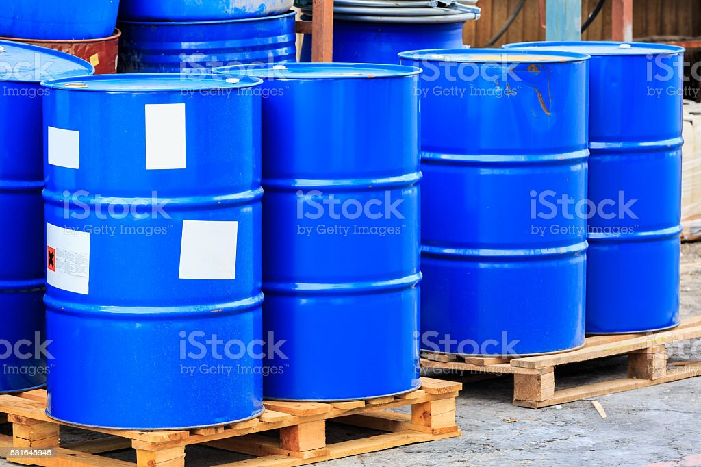 Many blue barrels on wooden pallets stock photo