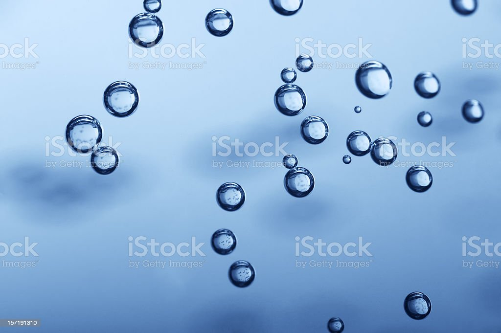 Many bubbles floating to the top of blue water royalty-free stock photo