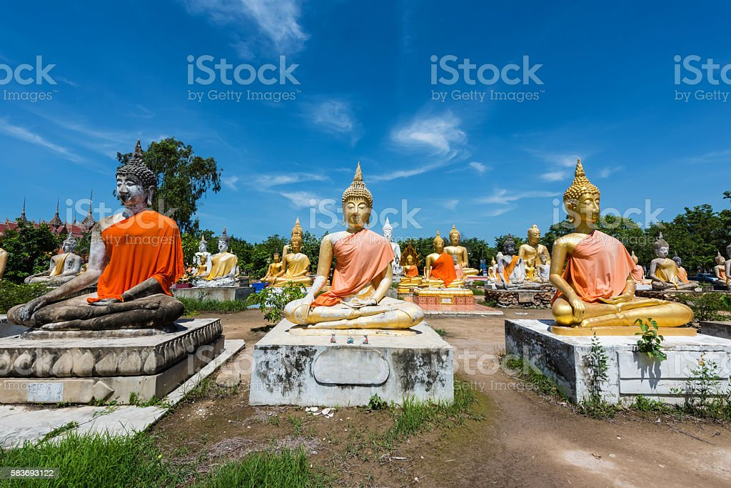Many Budddha statues against blue sky stock photo