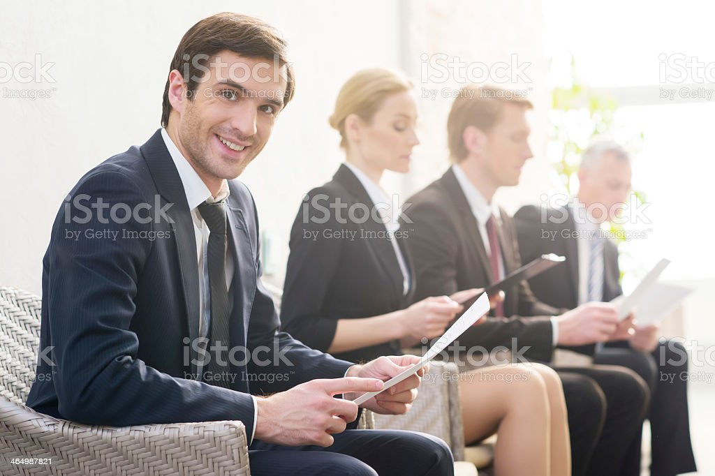 Many business people sitting in chairs and looking at papers stock photo