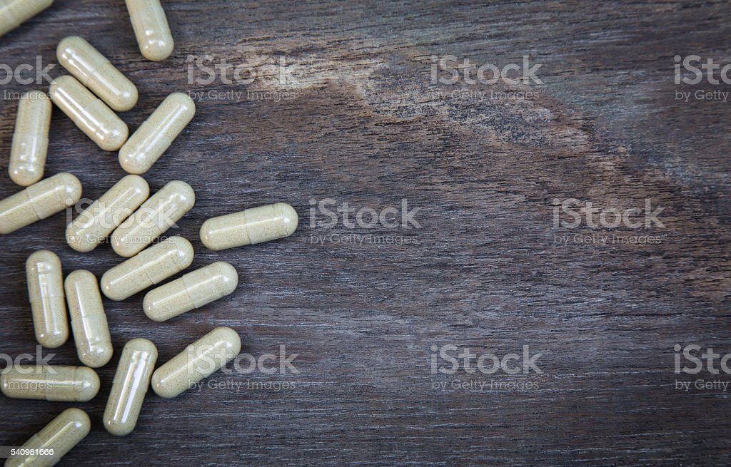 many capsule pill on wooden background stock photo