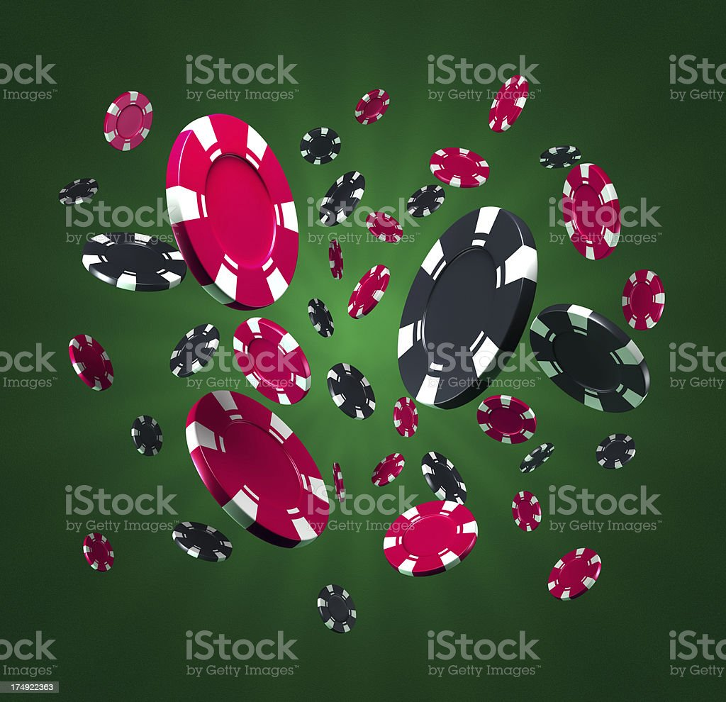Many casino tokens flying on green background stock photo