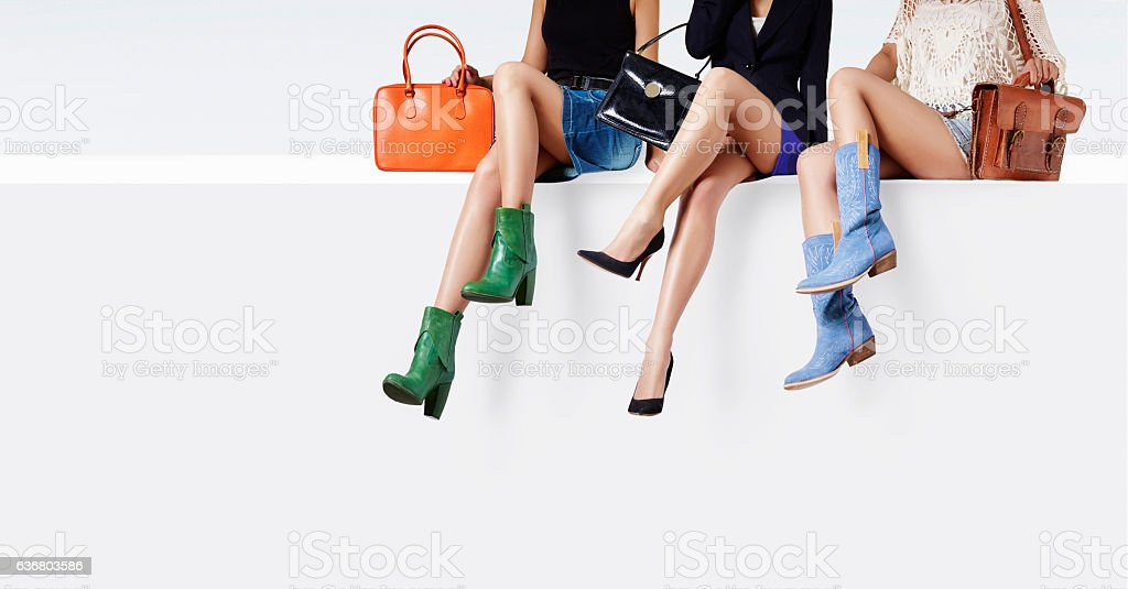 Many colorful bags and shoes women sitting together. stock photo