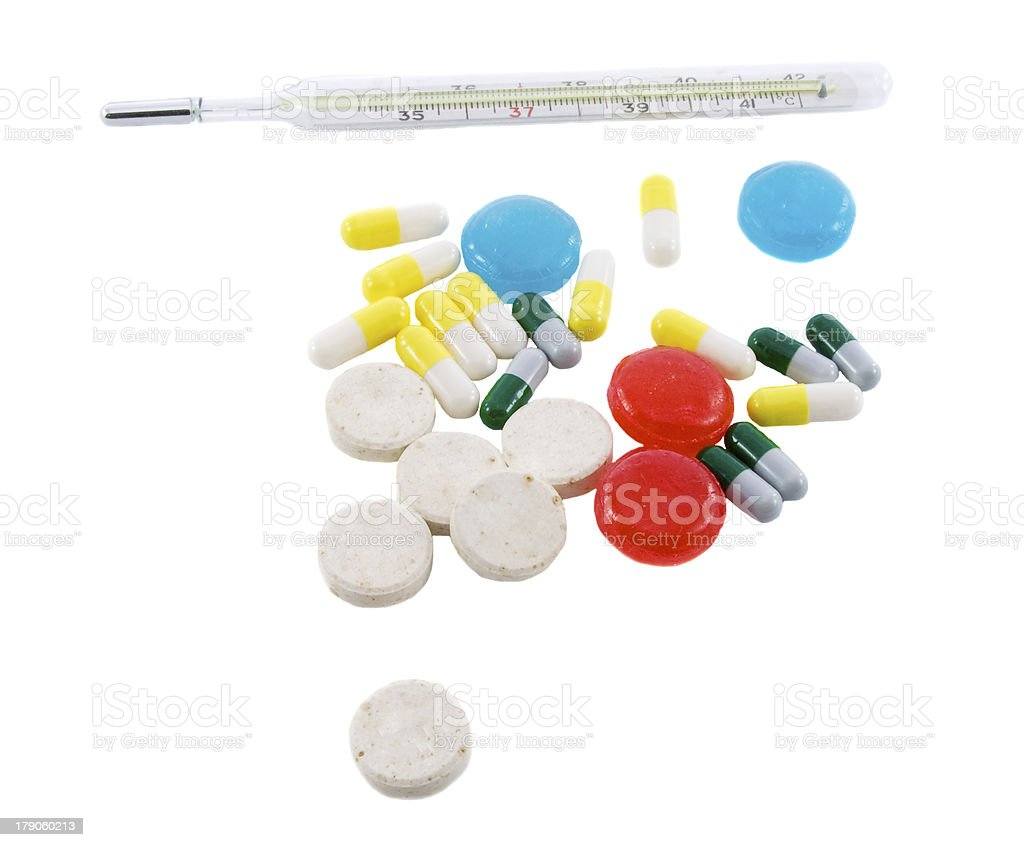 Many different color tablets, pills and thermometer isolated ove royalty-free stock photo