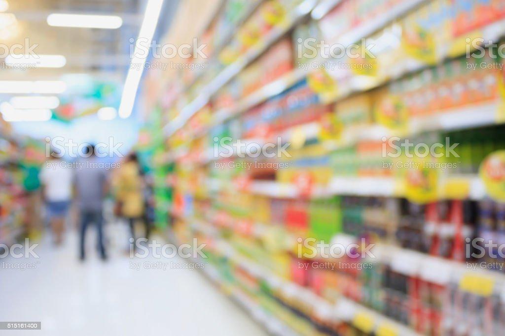 Many different drink bottles on supermarket shelves blurred background stock photo