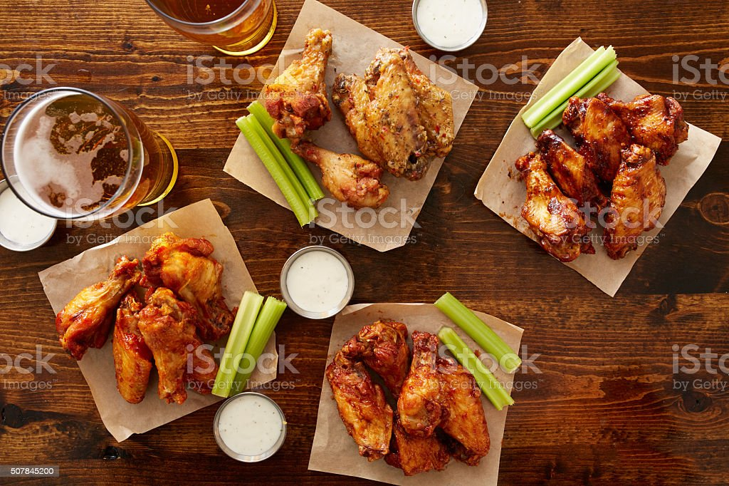 many different flavored buffalo chicken wings with beer stock photo