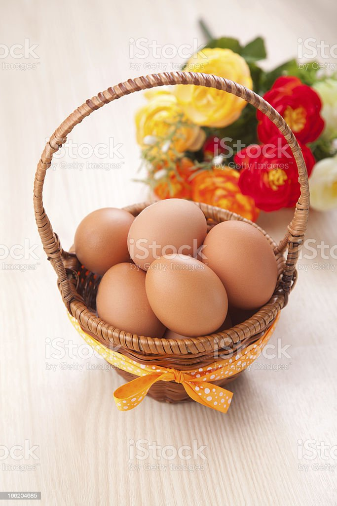 many eggs in little basket with flowers on wooden table royalty-free stock photo