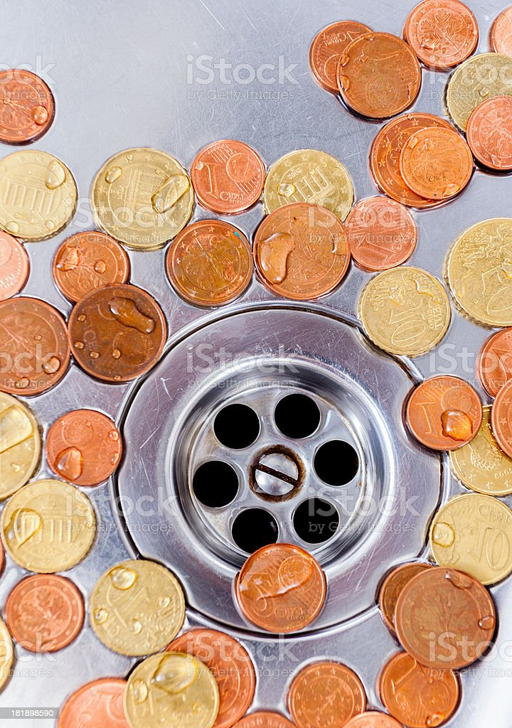 Many euro coins laying in a dry silver kitchen sink. royalty-free stock photo