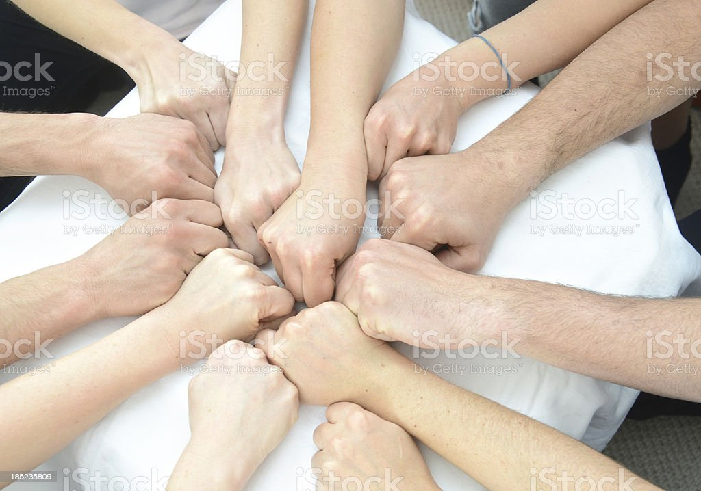 many fists coming together in the middle royalty-free stock photo