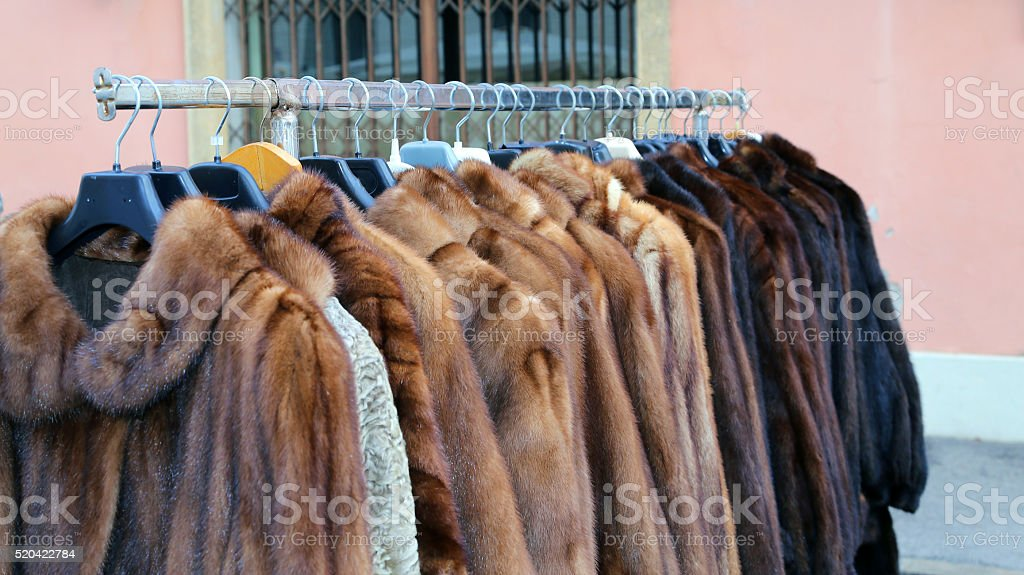 many fur coat for sale in the flea market outdoors stock photo