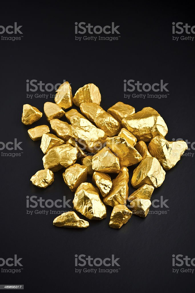 Many gold nuggets on a black background. stock photo