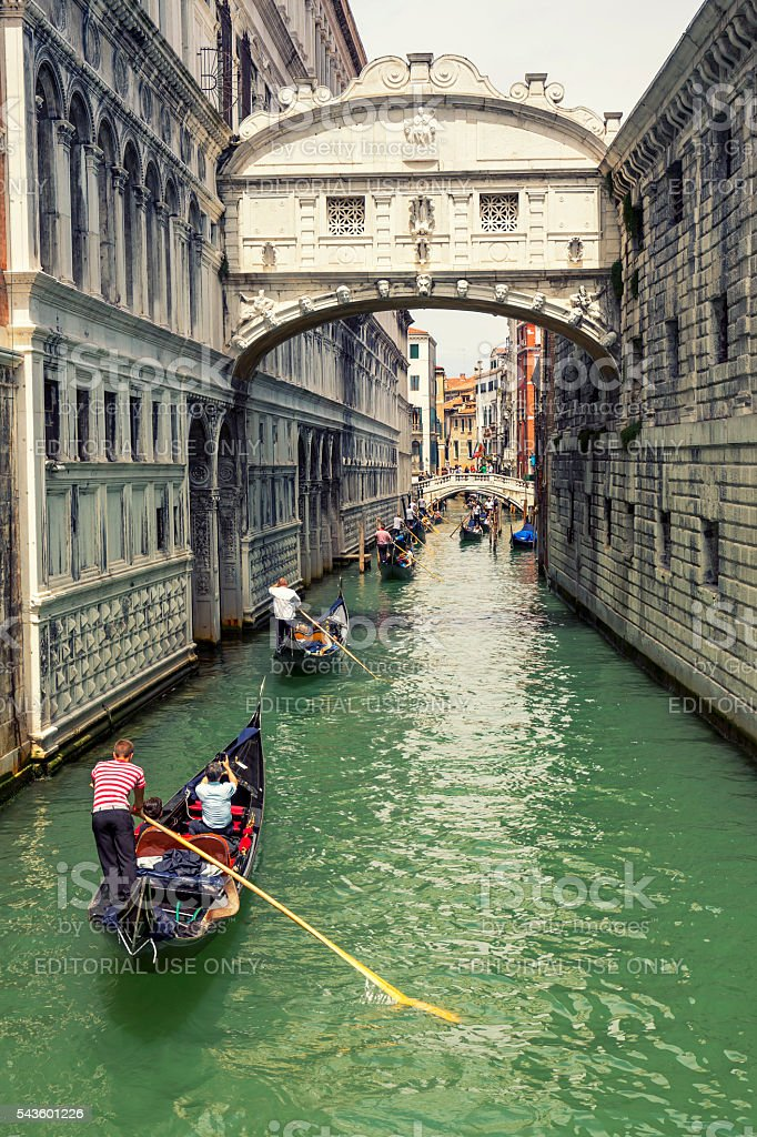 Many gondolas navigating under the Bridge of Sighs in Venice stock photo