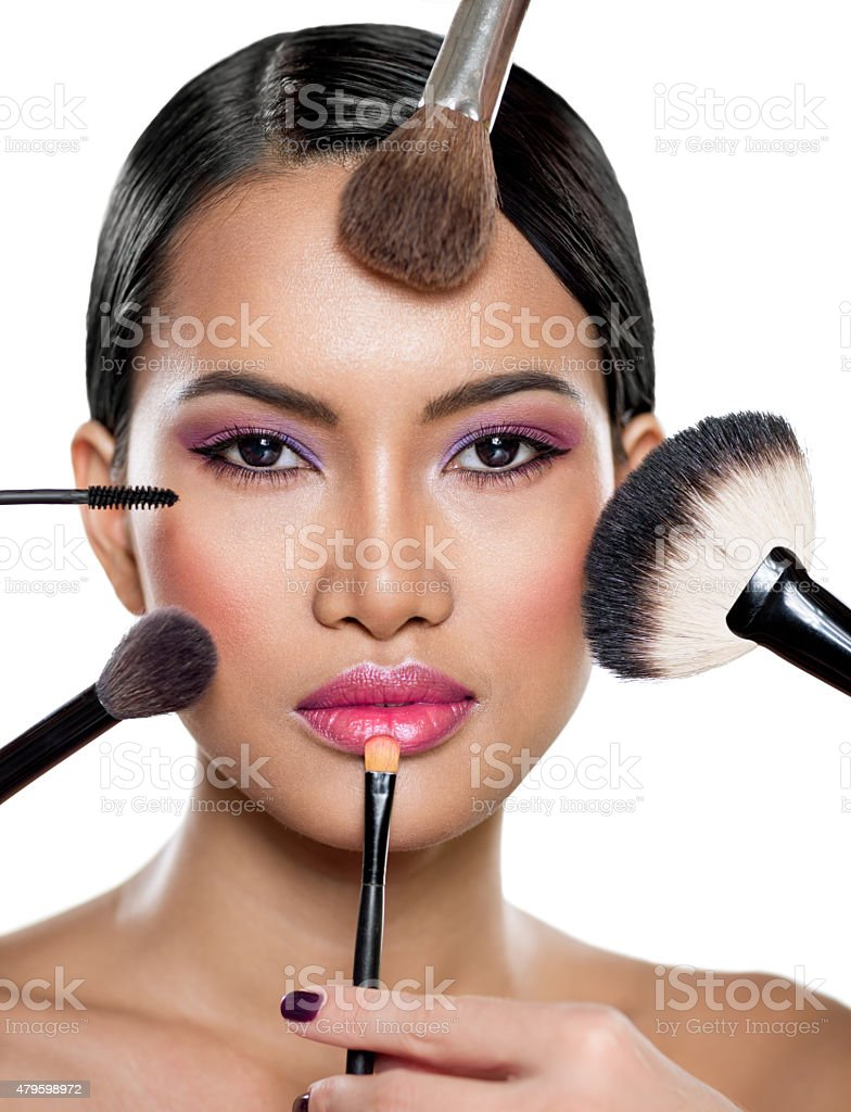 many hands applying make up on a woman stock photo