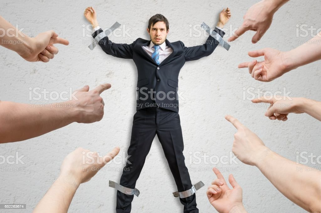 Many hands blame employee who is taped to the wall. stock photo