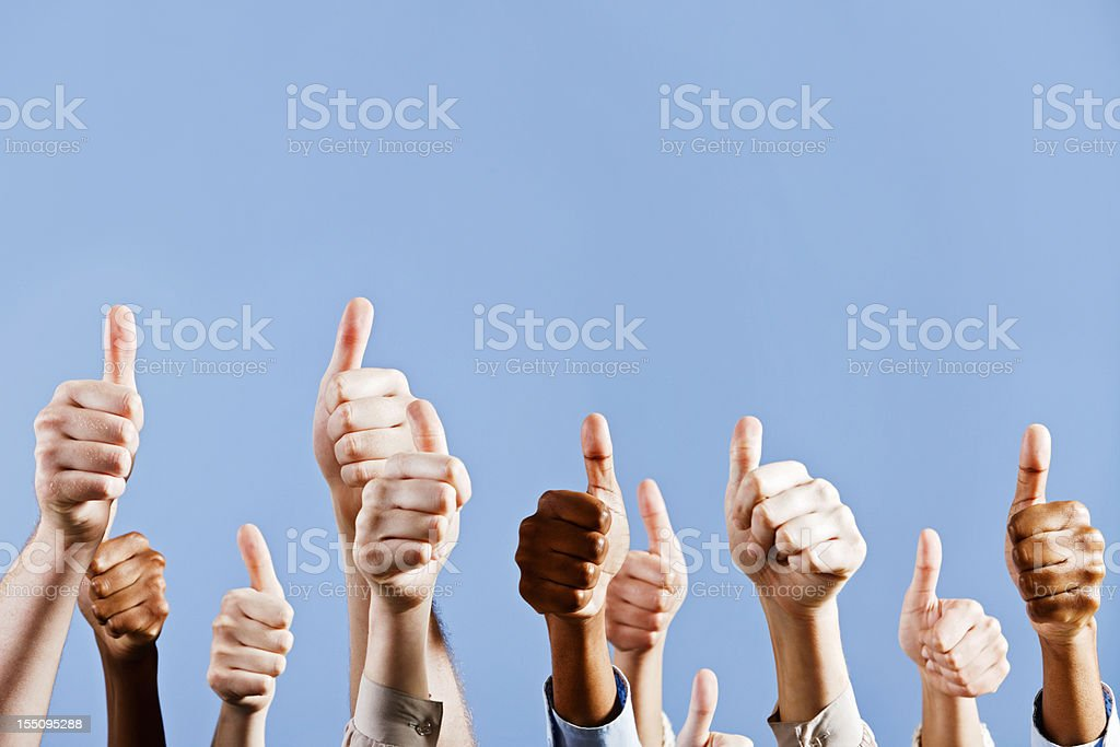Many hands give approving thumbs up against blue background royalty-free stock photo