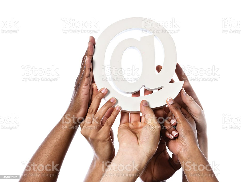 Many hands hold up a white @ sign royalty-free stock photo
