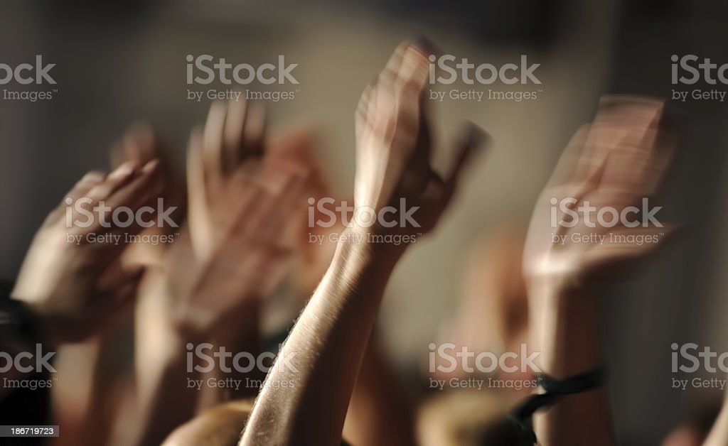 Many hands raised in motion in a large crowd of people royalty-free stock photo