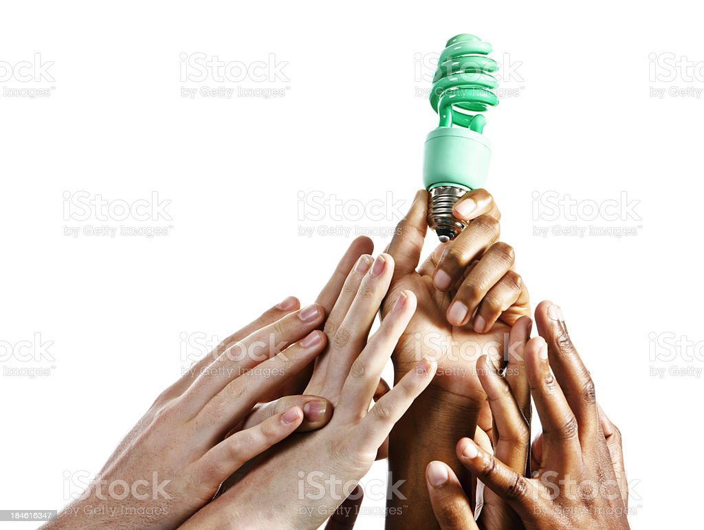 Many hands reach for green compact fluorescent light bulb royalty-free stock photo
