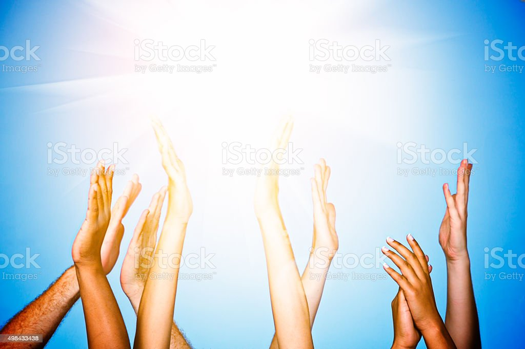 Many hands reaching up to Heaven or the Sun stock photo