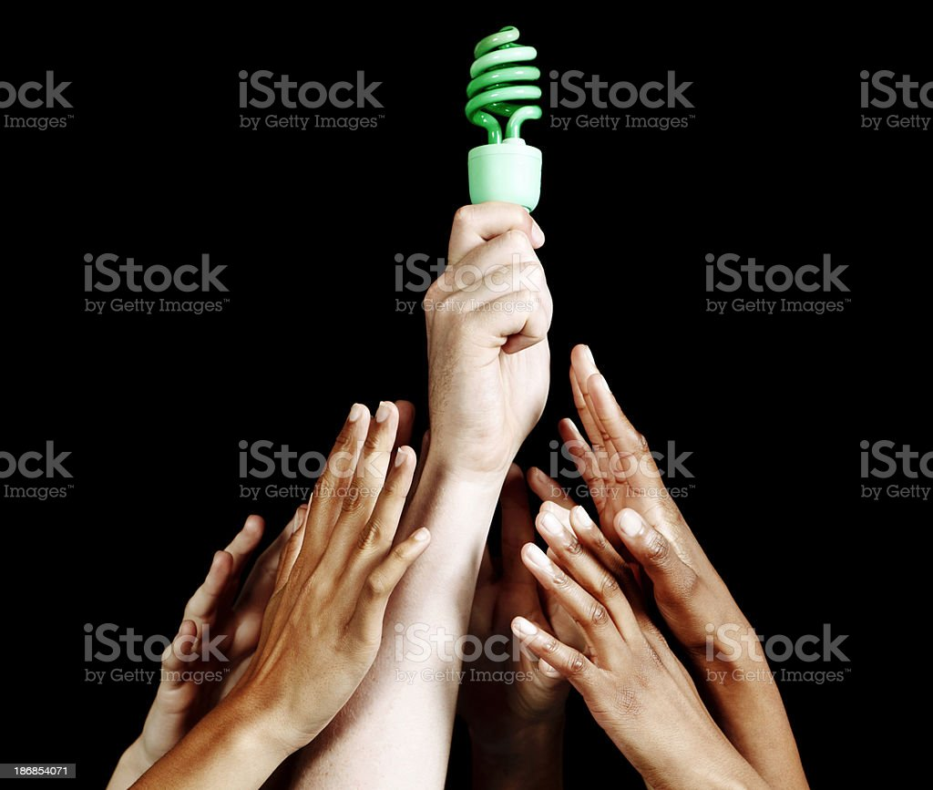 Many hands reaching up towards unlit green lightbulb against black stock photo
