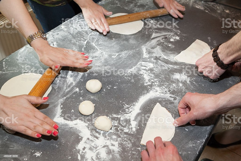 Many hands rolling dough stock photo