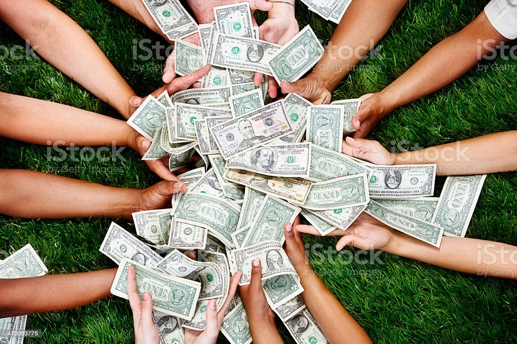Many hands stretched out to catch multiple dollar bills stock photo
