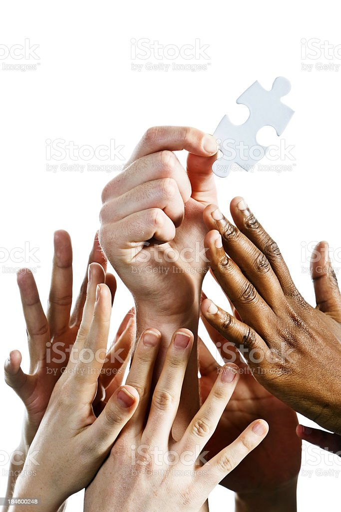Many hands vie for last piece of jigsaw puzzle royalty-free stock photo