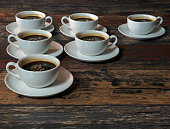 Many identical white cups of coffee