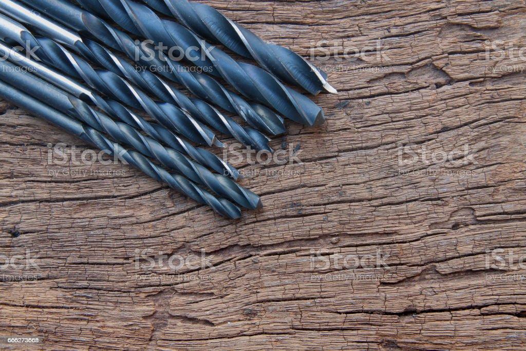 Many iron drill bit on wood background stock photo