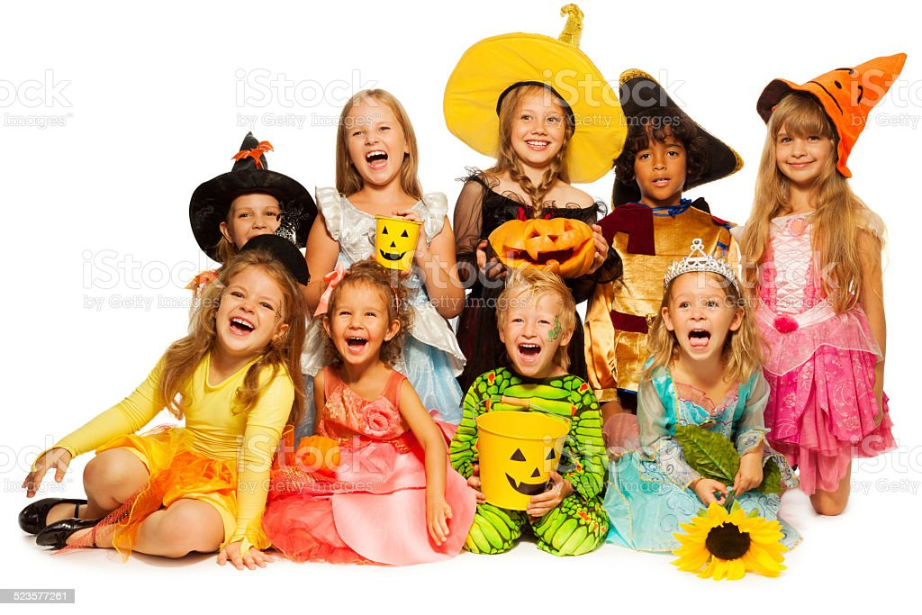 Many kids sit in group wearing Halloween costumes stock photo