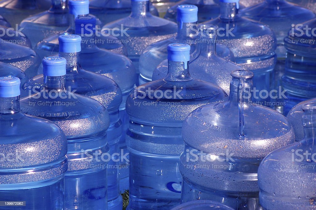 Many large blue water jugs some with caps stock photo