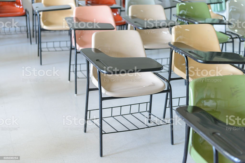 Many lecture chairs arranged neatly in empty classroom. stock photo