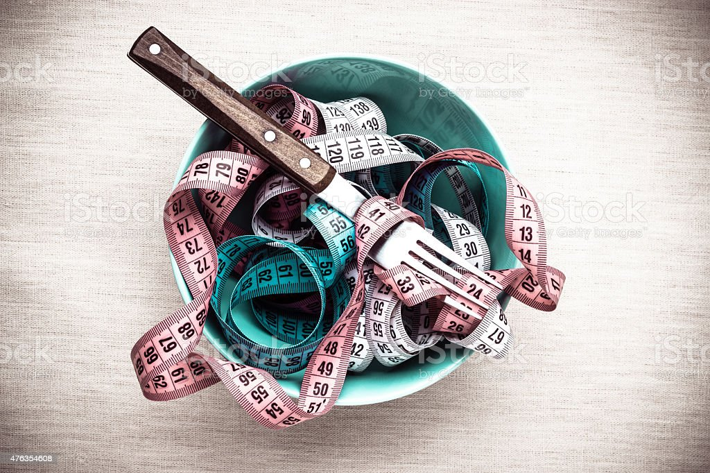 Many measuring tapes in bowl on table stock photo
