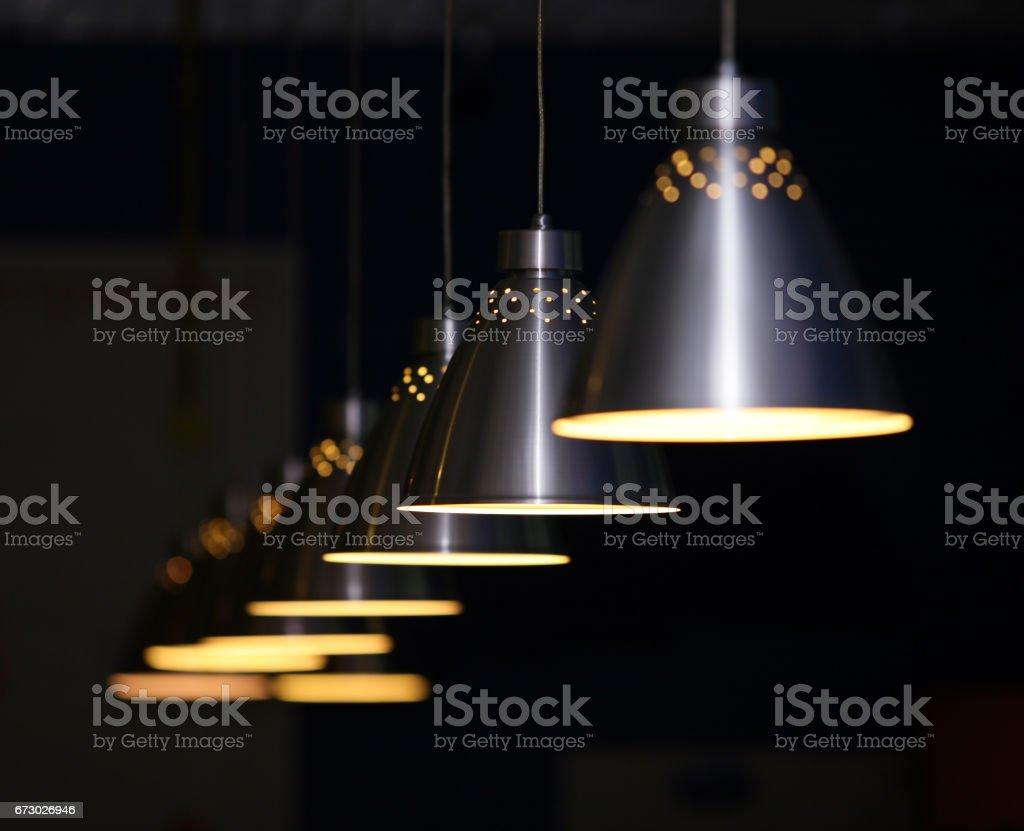 Many metal lamps at dark restaurant stock photo