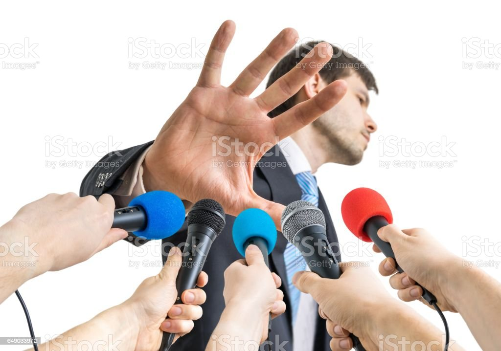 Many microphones in front of politician who shows no comment gesture. stock photo