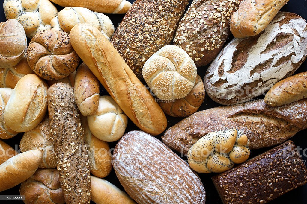 Many mixed breads and rolls shot from above. stock photo