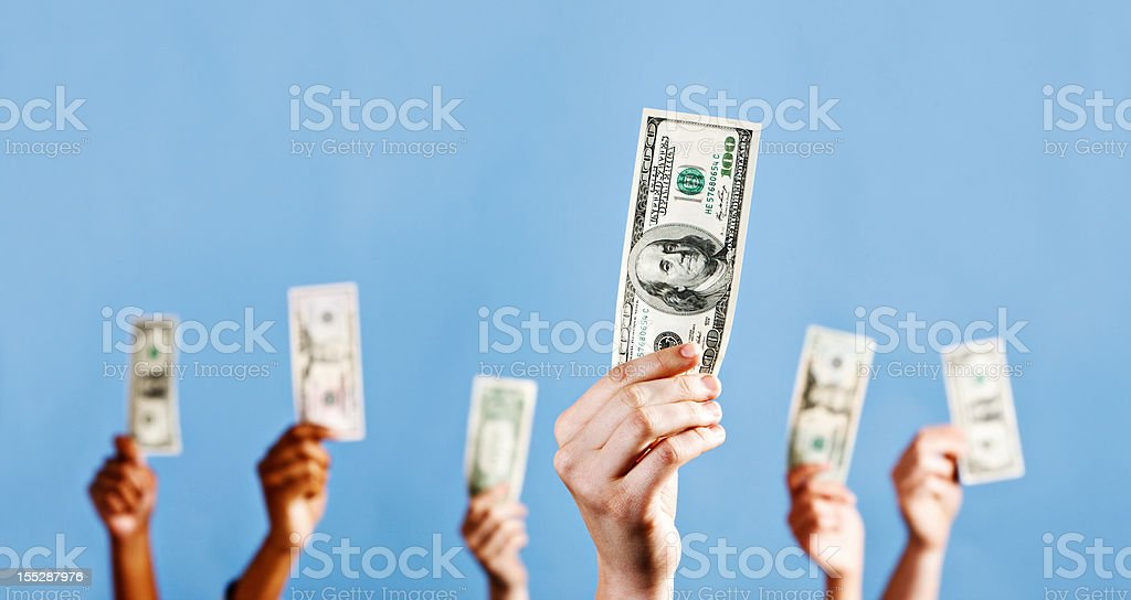 Many mixed hands hold up US dollars against blue stock photo