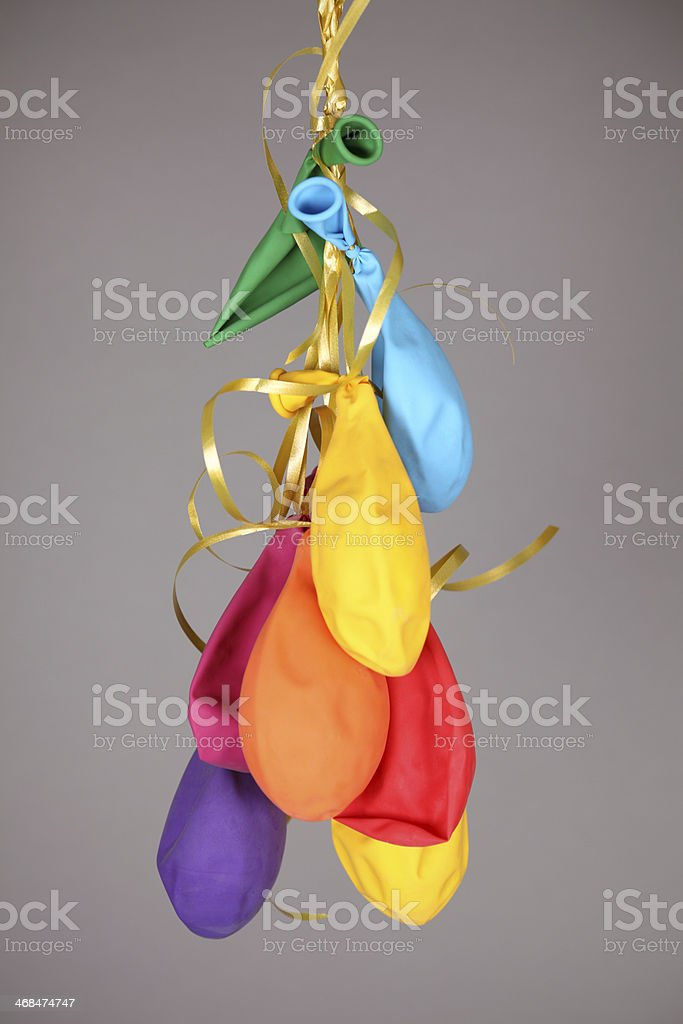 Many multicolored deflated balloons tied to a ribbon stock photo