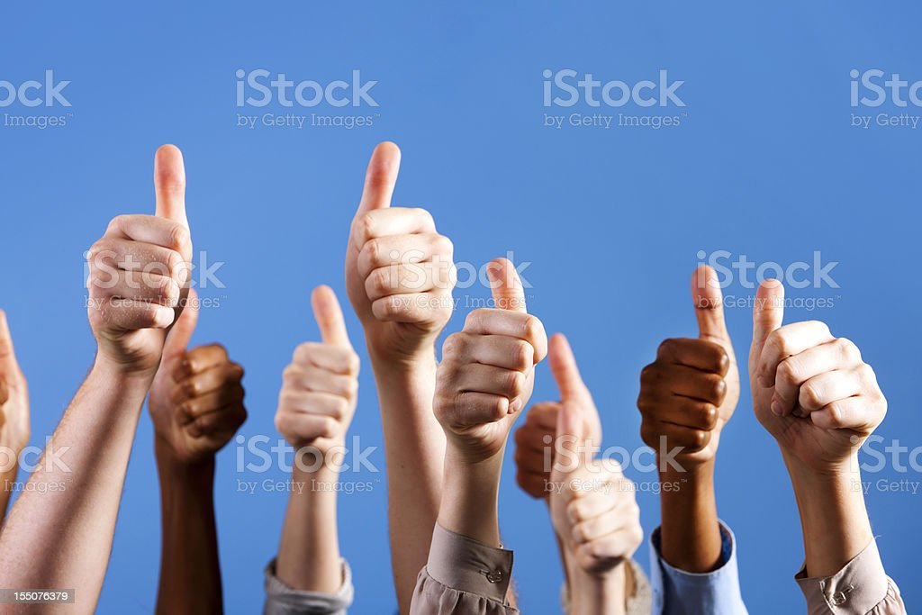 Many multiracial hands give group thumbs up of approval stock photo