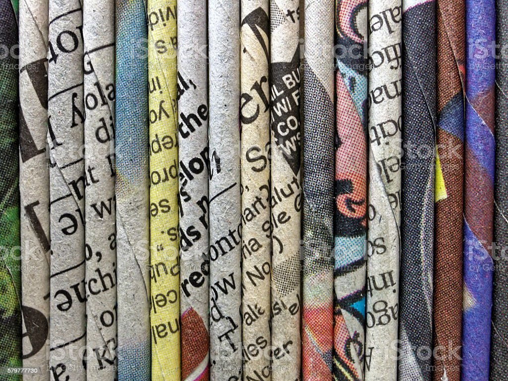 Many newspapers rolled and folded up lines up together stock photo