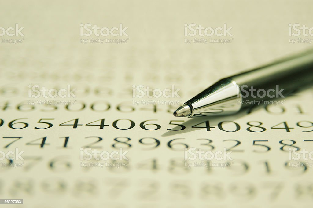 Many numbers typed on white paper, pen lying on top of paper royalty-free stock photo
