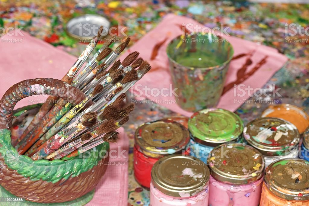 Many Paintbrushes And Paint In The Jar On The Palette stock photo