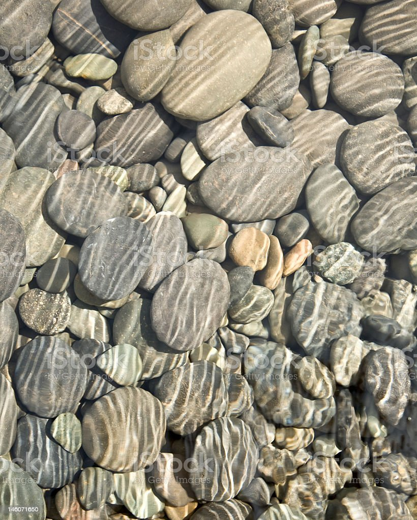 Many pebbles and stones in shallow water stock photo